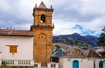 In Ecaduor – a tower and building roof tops against a background of mountains