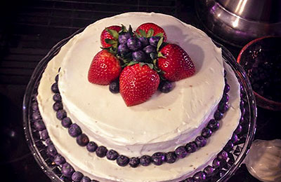 White frosted cake decorated with strawberries and blueberries