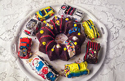 Platefull of little cakes made to look like cars, with a star-shipped cake in the center