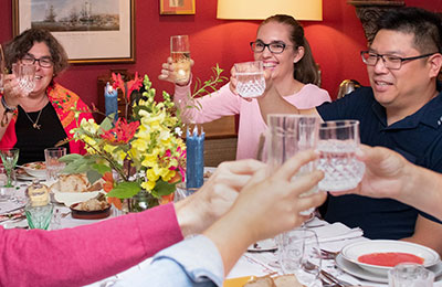 Group dinner guests smile as they hold up their glasses for a toast