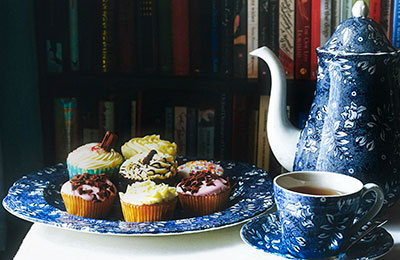 Tea setting with teacup, teapot and pastries