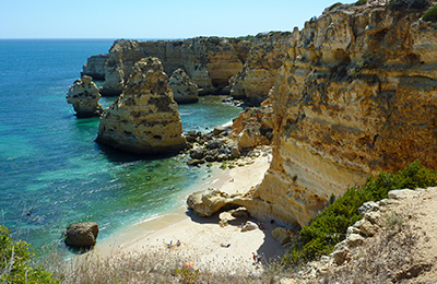 Rocky cliffs and turquoise water at this Portugal beach.