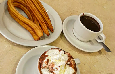 Churros, coffee and hot chocolate on a table.