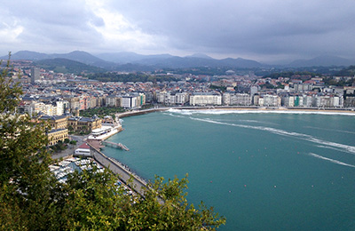 Overlooking the water and San Sebastian with mountains in the background.