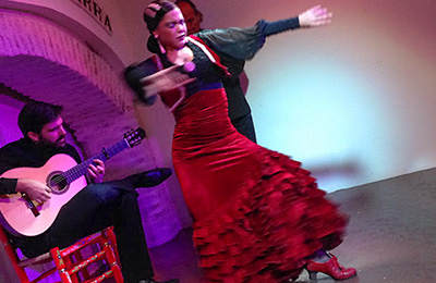 A Flamenco dancer with a guitarist sitting nearby.